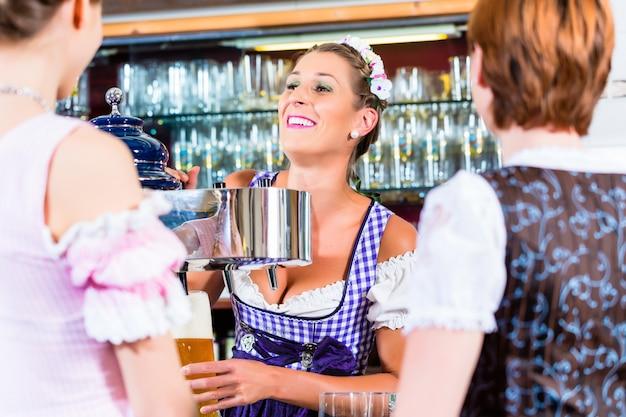 Хозяин гостиницы в баварском пабе с покупателями