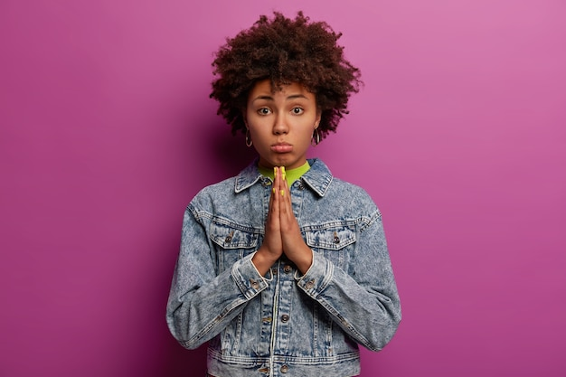 Innocent dark skinned woman keeps palms pressed together, looks with imploring sad expression, pleads for something, wears denim jacket, poses against purple wall. please, help me once again
