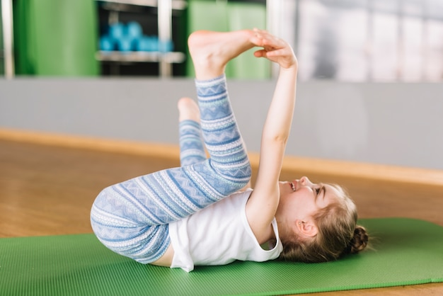 Innocent girl child practicing yoga in fitness center
