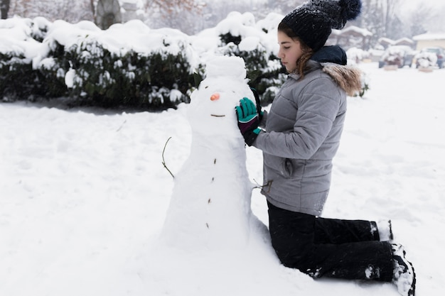 Innocent girl touching snowman in winter