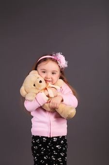 Innocent little girl playing with a bear