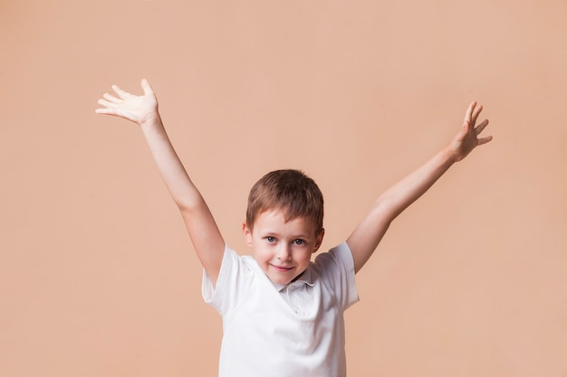 Innocent smiling boy with hand raised standing in front of beige background