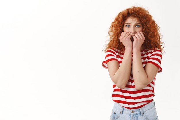 無邪気な臆病な赤毛の巻き毛の女性青い目パニックに見える心配そうに見えるおびえたホールド手口を噛む指の爪震える恐怖凝視カメラ恐怖、立っている白い壁