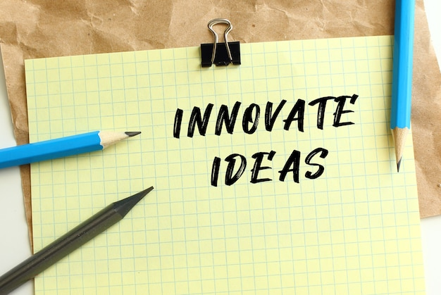 Innovate ideas lettering on a yellow sheet of paper over crumpled kraft paper. pencils and paper clip. business concept.