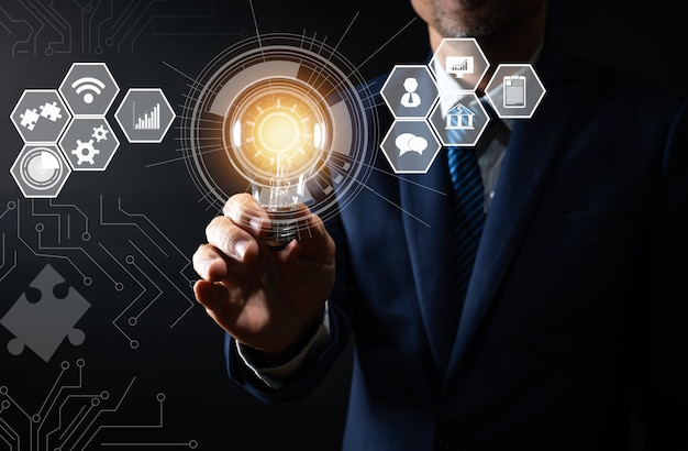 Инновации и технологии, бизнесмен держит лампочку креативного и соединительную линию