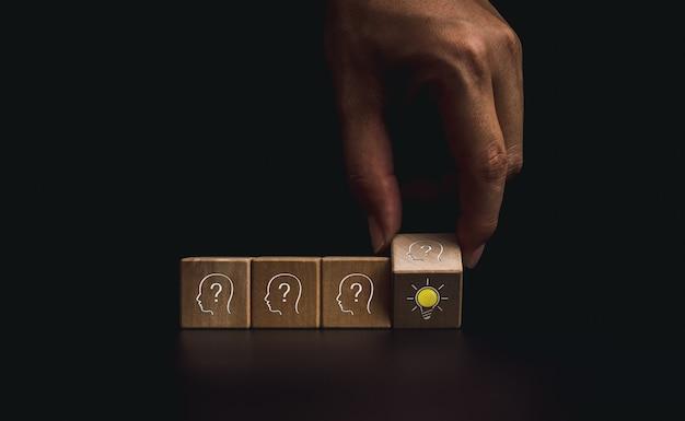 イノベーション、結論、スマートラーニング、知識、創造的なアイデアのコンセプト。暗い背景、最小限のスタイルで頭の人間のシンボルと電球のアイコンで木製の立方体ブロックをめくってクローズアップの手。