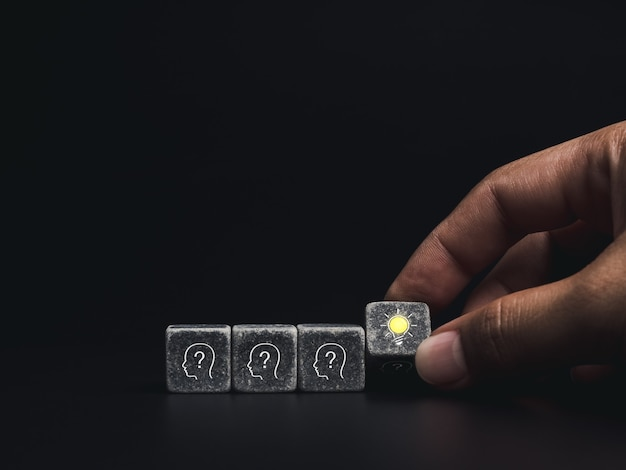 Innovation, conclusion, smart learning, knowledge and creative idea concept. close-up hand flipping over black dice block with head human symbol and light bulb icon on dark background, minimal style.