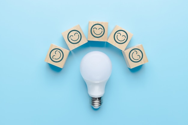 Innovation and idea concept, smile icon on cube box with light bulb on blue background