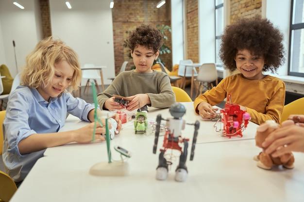 혁신은 테이블에 앉아서 로봇 장난감을 확인하면서 웃고 있는 호기심 많은 다양한 소년들