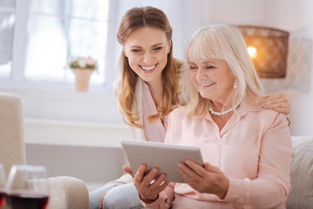 Инновационное устройство. счастливая позитивная пожилая женщина, сидящая вместе со своей дочерью и держащая в руках планшет, пользуется этим современным устройством