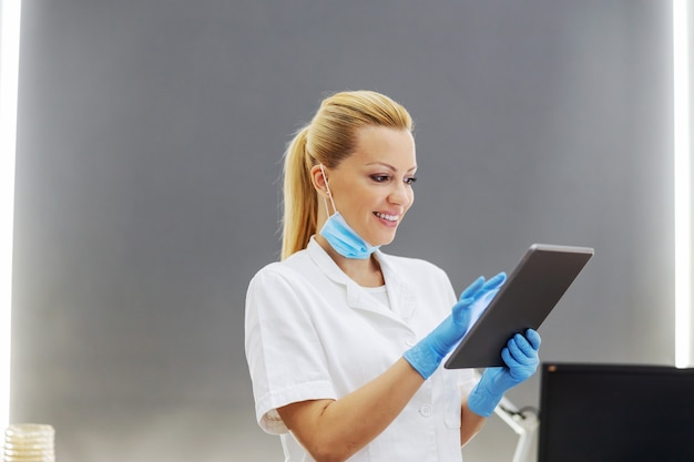 실험실에 서서 태블릿을 사용하여 테스트 결과를 입력 할 때 수술 용 마스크와 고무 장갑을 착용 한 흰색 멸균 유니폼을 입은 혁신적인 경험이 풍부한 여성 실험실 조교.