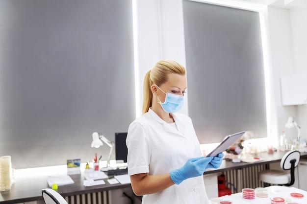 Инновационная опытная женщина-лаборант в белой стерильной форме с хирургической маской и резиновыми перчатками стоит в лаборатории и использует планшет для ввода результатов теста.