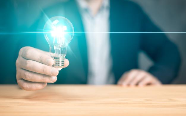파란색 플레어가 있는 전구를 들고 있는 사업가 손의 혁신적인 아이디어