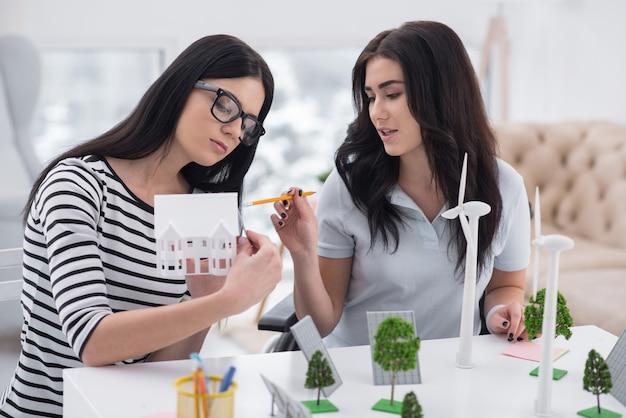 Инновационное планирование. задумчивая женщина-инвалид и коллега позируют за столом и работают с моделями альтернативной энергетики