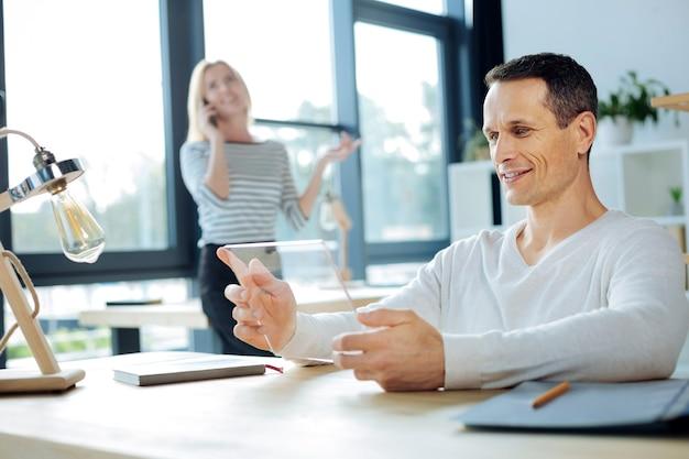 革新的なタブレット。タブレットを持って、オフィスでの仕事にそれを使用しながら笑顔のハンサムな魅力的なポジティブな男