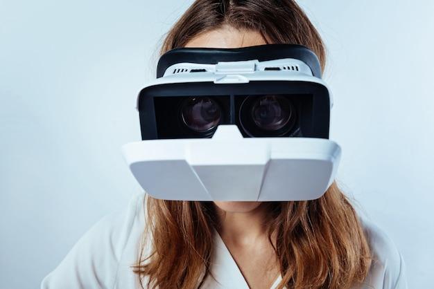 革新的なテクノロジー。ビジュアルリアリティメガネを試着し、バックグラウンドでゲームをプレイしている若い女性の拡大された外観。