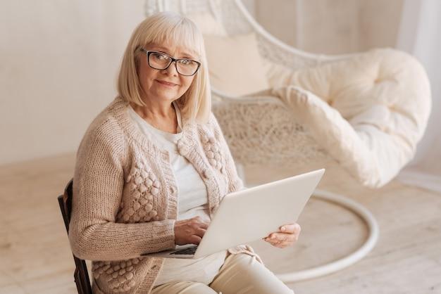 Инновационная технология. веселая приятная пожилая женщина сидит на стуле и смотрит на вас во время работы на ноутбуке