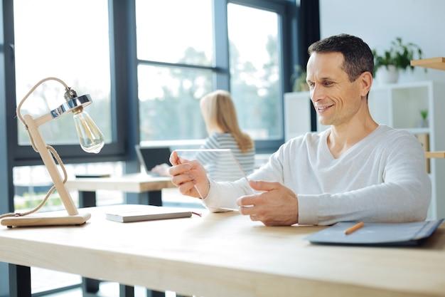 革新的なテクノロジー。テーブルに座って、オフィスで働いている間、現代のタブレットを使用してポジティブで陽気な素敵な男