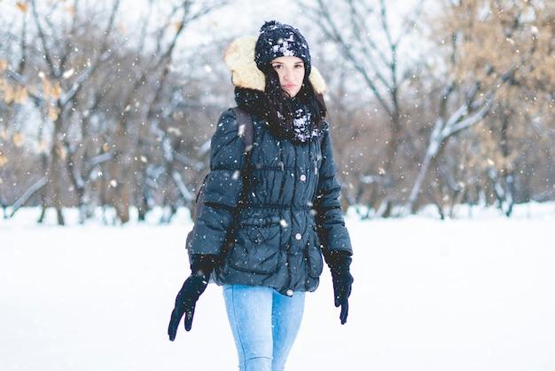 冬の雪の日にinorest自然を歩く若い女性
