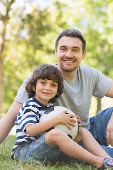 Отец и сын с футболом, сидящим на траве inpark