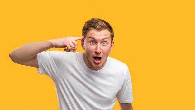 Безумный жест. умопомрачительный. потрясенный человек с пальцем на виске, изолированном на оранжевом фоне.