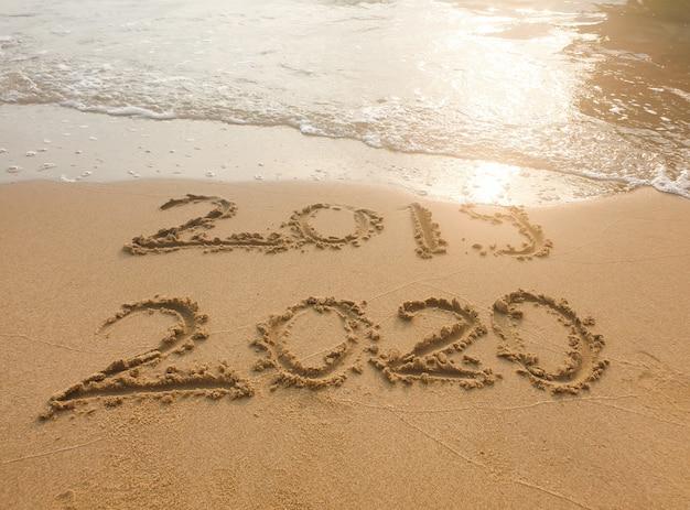 Надпись 2019 и 2020 на песчаном пляже.