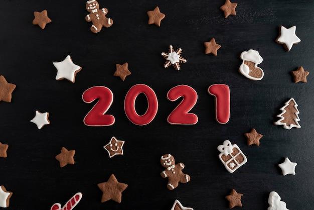 ジンジャーブレッドクッキーからの碑文2021。黒の背景の上面図にクリスマスのお菓子。