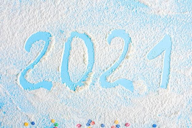 Надпись 2021 из муки на синем столе. плоская планировка