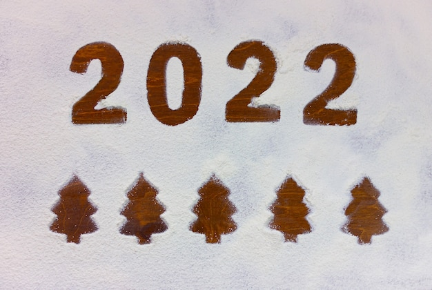 Inscription 2022 and christmas trees drawn on flour on a wooden table.