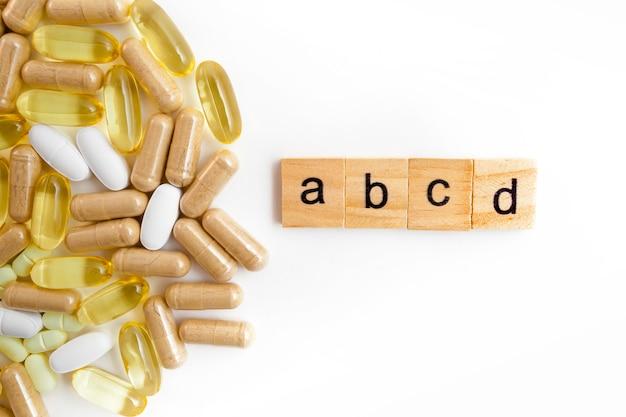 さまざまな錠剤の白い背景の上の木製の立方体の碑文abce