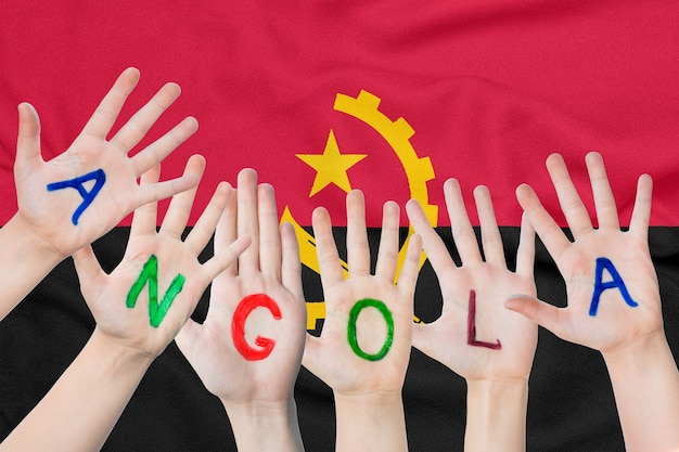 Inscription angola on the children's hands against the background of a waving flag of the angola