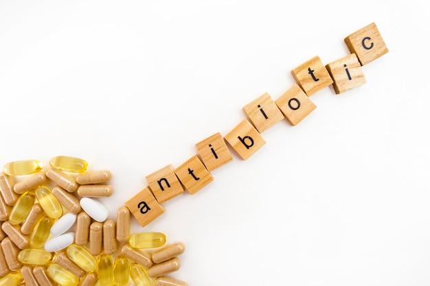 Надпись антибиотики в деревянных кубиках на белом фоне различных таблеток