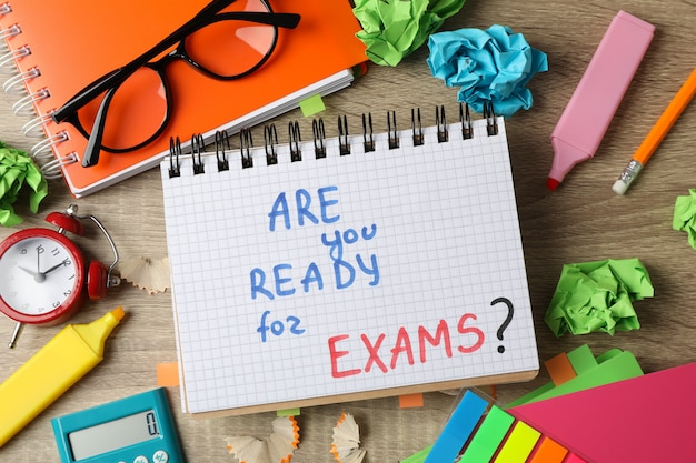 Inscription are you ready for exams? and different stationary on wooden, top view