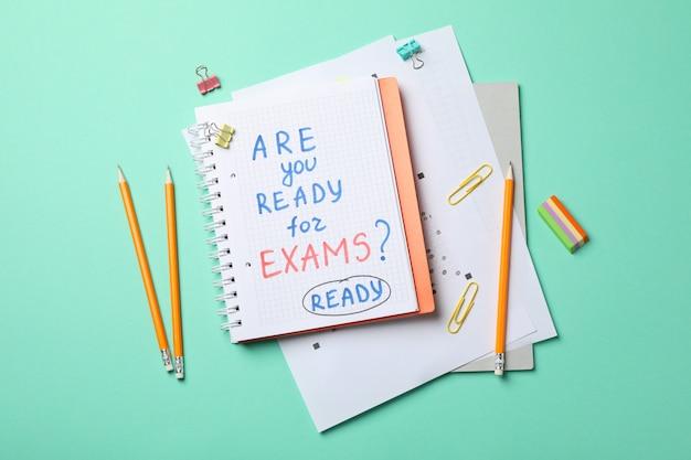 Надпись готовы ли вы к экзаменам? готовые и стационарные на мятном столе, вид сверху