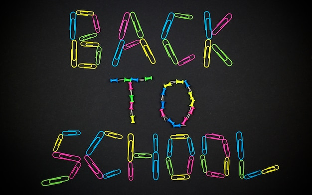 Inscription back to school on the background blackboard made of colorful paper clips