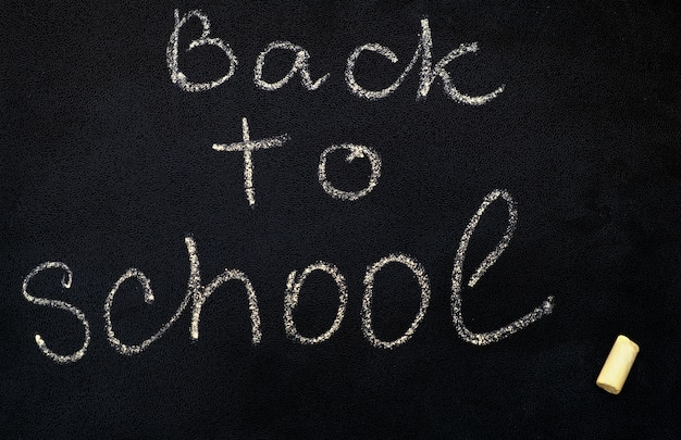 Inscription back to school on black chalkboard, close up.