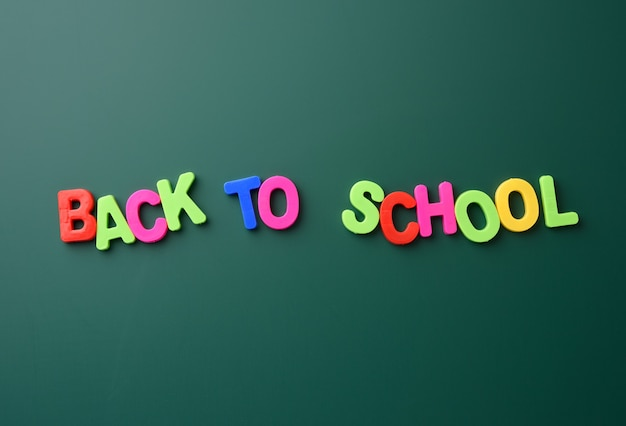 Inscription back to school from multicolored plastic letters on green chalk board