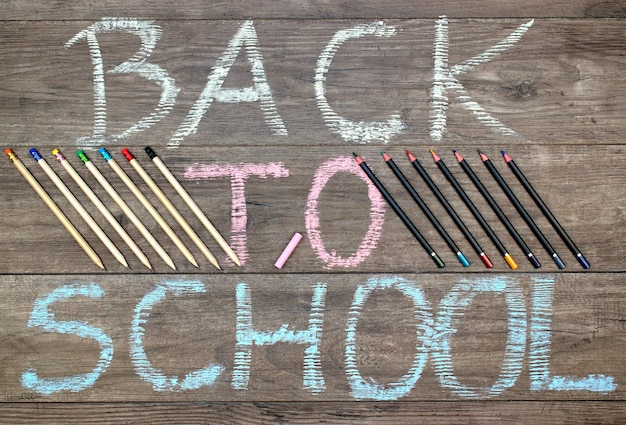 Inscription back to school,pencils and crayons on a wooden background