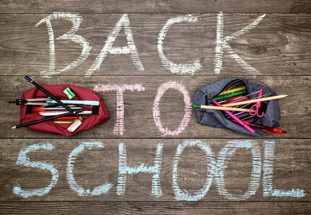 Inscription back to school and two pencil-cases with school accessories