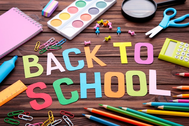 Inscription back to school with school supplies on brown wooden  surface