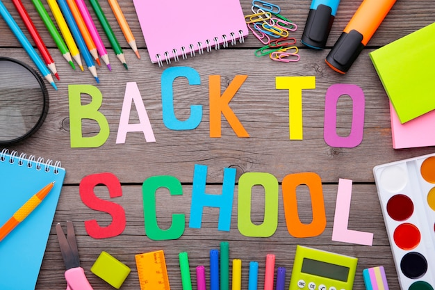 Inscription back to school with school supplies on grey wooden background