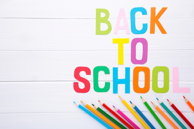 Inscription back to school with school supplies on white wooden background