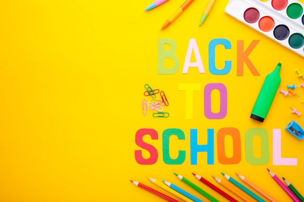 Inscription back to school with school supplies on yellow background. colorful letters