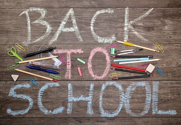 Inscription back to school with school tools on a wooden background