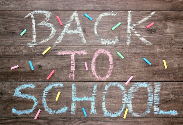Inscription back to school on a wooden background and colored chalk