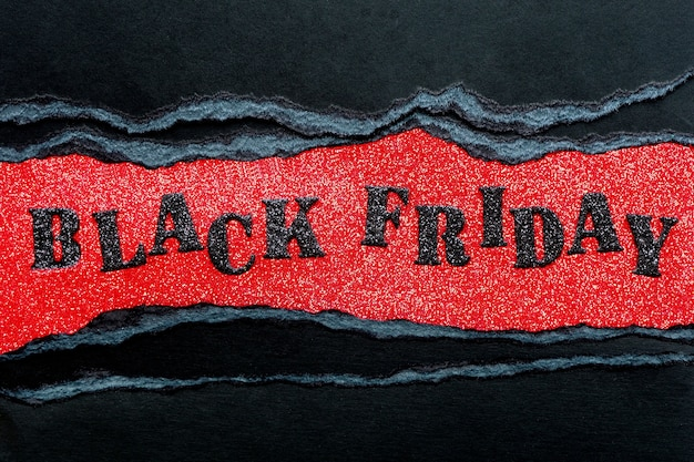 빨간 반짝이 배경 및 찢어진 된 가장자리와 골 판지의 검은 시트에 검은 빛나는 편지에서 비문 검은 금요일.