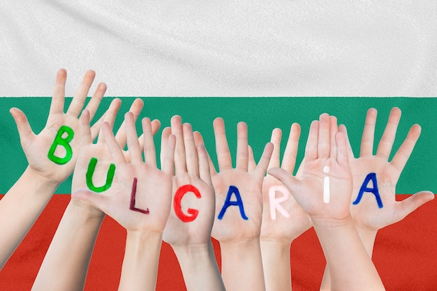 Inscription bulgaria on the children's hands against the surface of a waving flag of the bulgaria