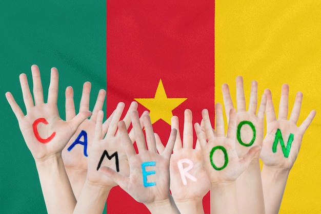 Inscription cameroon on the children's hands against the background of a waving flag of the cameroon