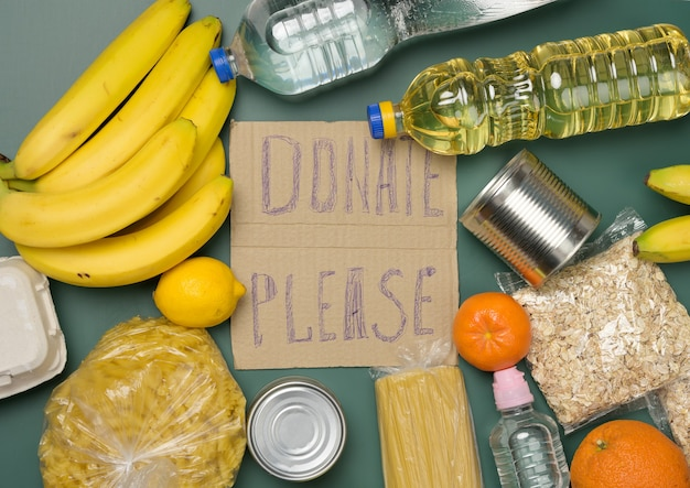 Inscription on the cardboard please donate various products. fresh fruits, pasta and canned food, top view