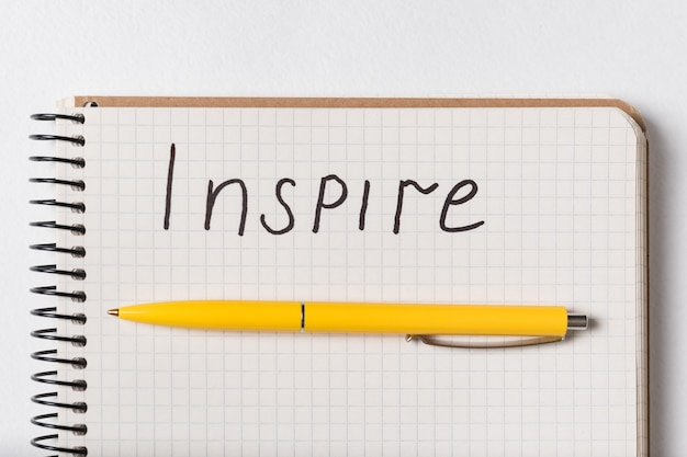 Inscription in copybook inspire. close up notepad and pen on white background